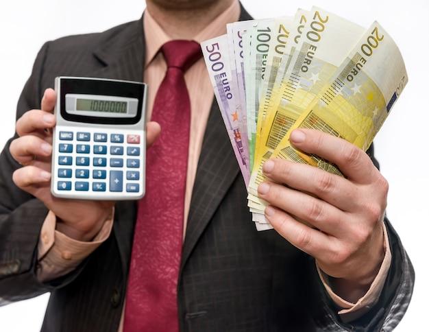 Calcolatrice della holding dell'uomo d'affari e banconote in euro isolate su bianco