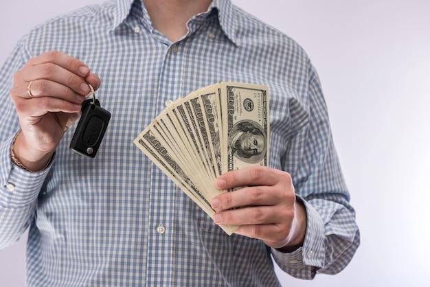 Chiave dell'automobile della tenuta dell'uomo d'affari e soldi del dollaro isolati. concetto di vendita