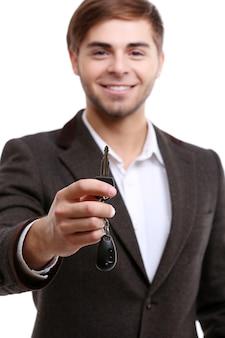 Uomo d'affari che tiene la chiave della macchina isolata su white