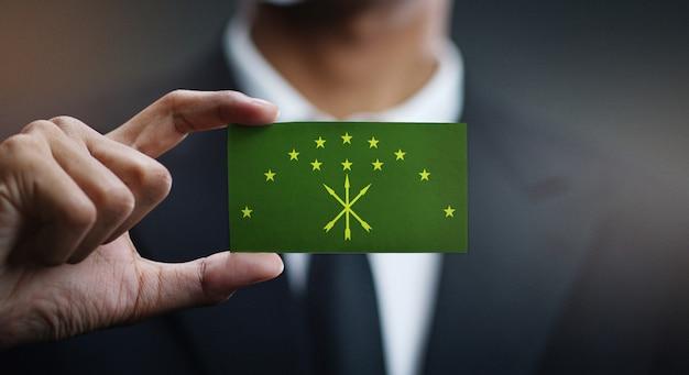 Uomo d'affari holding card of adygea flag