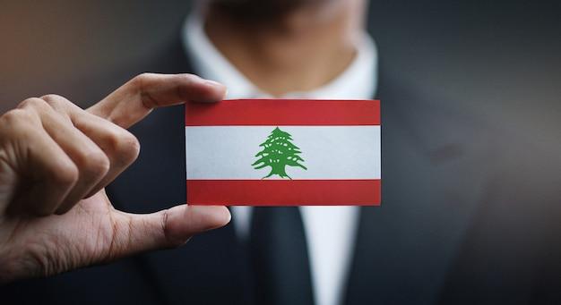 Uomo d'affari holding card of lebanon flag