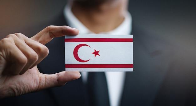 Uomo d'affari holding card della bandiera del nord cipro
