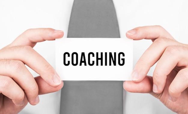 Imprenditore in possesso di una scheda con testo coaching, concetto di affari
