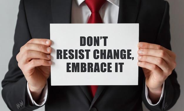 Uomo d'affari che tiene una carta con testo non resistere al cambiamento abbracciarlo