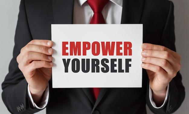 Uomo d'affari che tiene una carta con testo empower yourself