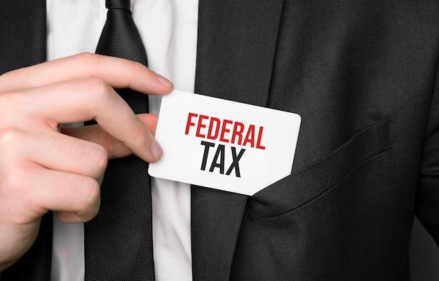 Uomo d'affari che tiene una carta con tassa federale del testo