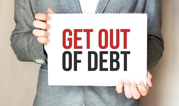 Uomo d'affari che tiene una carta con testo uscire dal debito