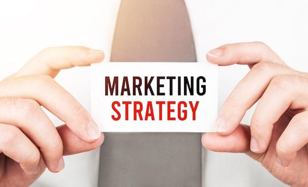 Uomo d'affari che tiene una carta con la strategia di marketing del testo, concetto di affari