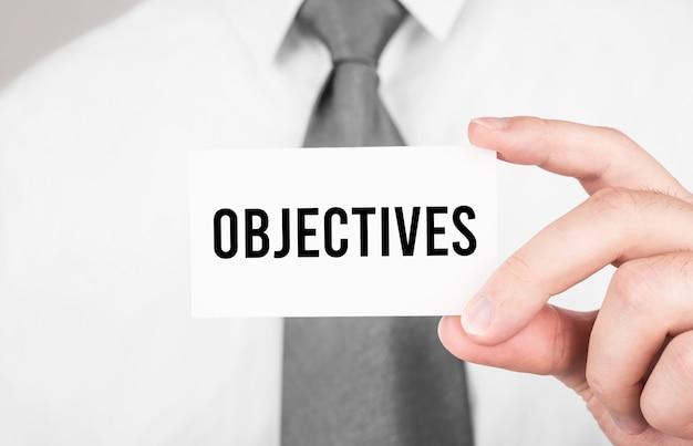 Uomo d'affari che tiene una carta con gli obiettivi del testo, concetto di affari