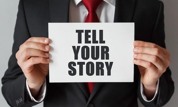 Uomo d'affari che tiene una carta con testo racconta la tua storia