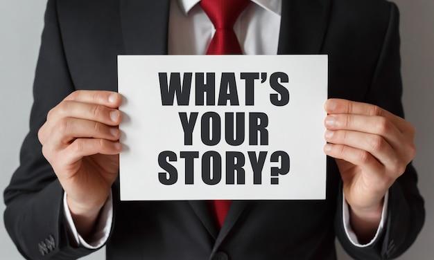 Uomo d'affari che tiene una carta con il testo qual è la tua storia