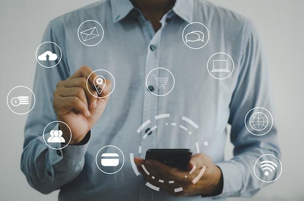 Uomo d'affari che tiene un telefono cellulare. concetto di big data della tecnologia di comunicazione aziendale, shopping online, schermo virtuale dell'icona di marketing online.