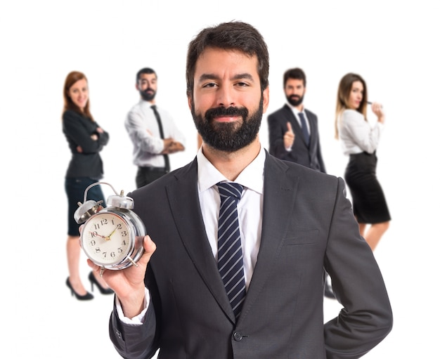 Uomo d'affari in possesso di un orologio su sfondo bianco