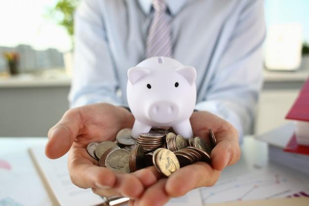 Monete e porcellino salvadanaio della tenuta dell'uomo d'affari