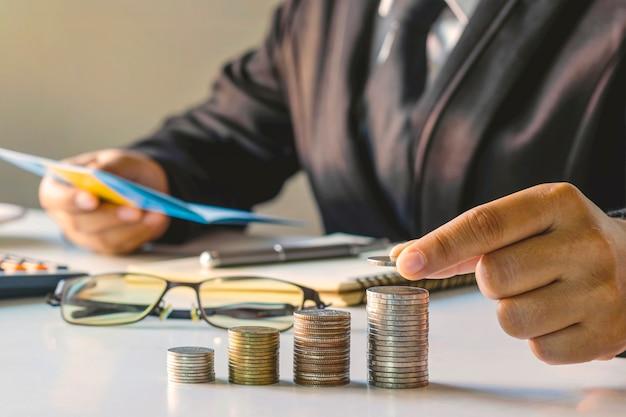 Imprenditore tenendo le monete su una pila di monete.