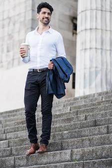 Uomo d'affari che tiene una tazza di caffè mentre va a lavorare all'aperto. concetto di affari.