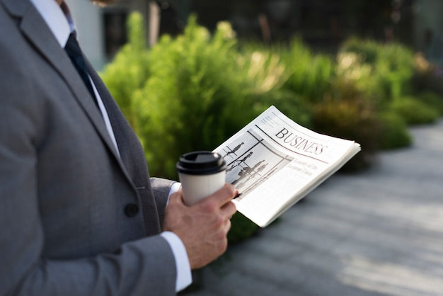 Uomo d'affari che tiene una tazza di caffè e leggendo un giornale
