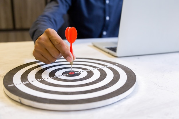 Uomo d'affari che tiene i dardi che puntano sul centro dell'obiettivo, concetto di successo di crescita di affari.