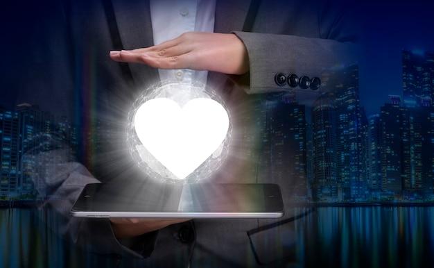 Uomo d'affari che tiene l'immagine digitale del cuore con cura concetto per servizi intelligenti post-vendita