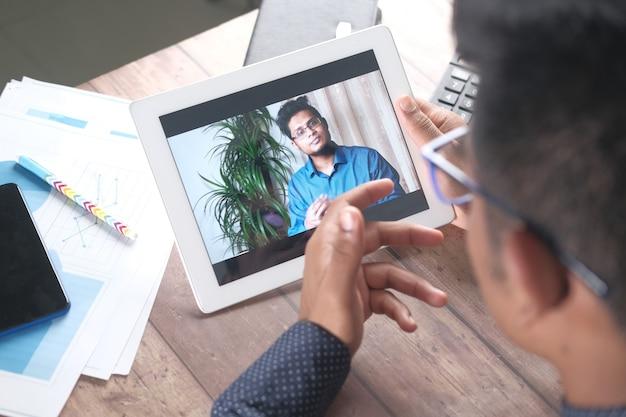 Imprenditore tenendo tavoletta digitale discutendo idee in videoconferenza