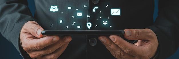 Uomo d'affari che tiene compressa digitale nelle sue mani con icone di contatto, comunicazione e posizione incandescente bianche che escono da esso in un'immagine concettuale.