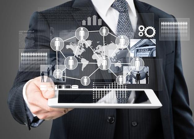 Uomo d'affari che tiene compressa digitale con icone di affari 3d