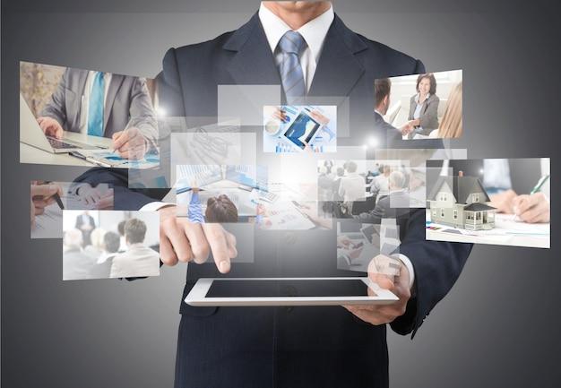 Uomo d'affari che tiene tablet digitale e lavora su uno schermo virtuale