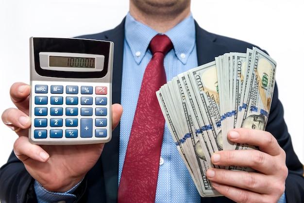 Uomo d'affari che tiene i dollari in ventilatore e calcolatrice