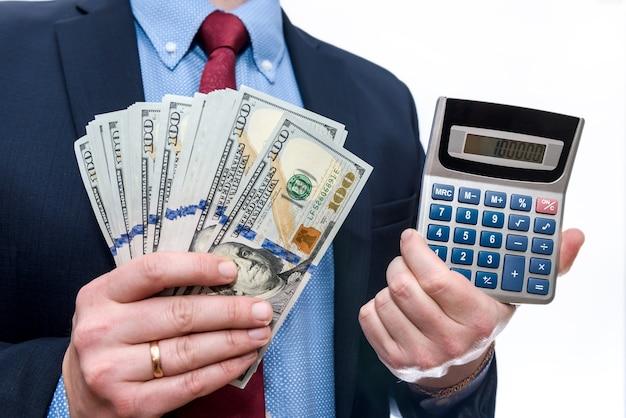 Uomo d'affari che tiene dollari nel ventilatore e nella calcolatrice