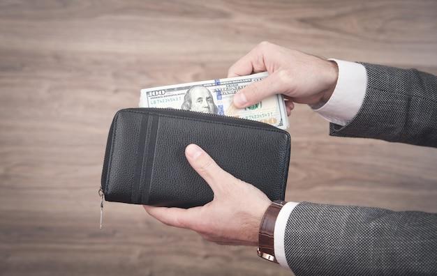 Uomo d'affari che tiene i dollari con il portafoglio.