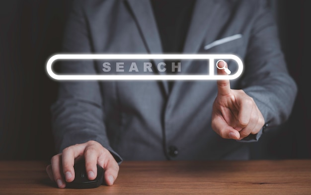Uomo d'affari che tiene il mouse elettronico e tocca il browser del motore di ricerca virtuale, concetto di tecnologia dell'informazione.