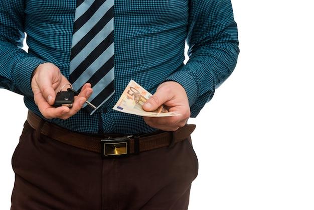 Uomo d'affari che tiene le banconote in euro e le chiavi della macchina isolate. acquista o noleggia il concetto di auto