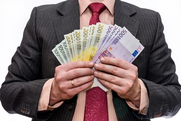 Uomo d'affari che tiene le banconote in euro a ventaglio isolato