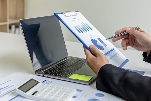 Uomo d'affari in possesso di documenti finanziari, possiede una società, sta controllando i documenti finanziari della società in ufficio, i documenti finanziari mostrano il formato grafico. concetto di gestione finanziaria.