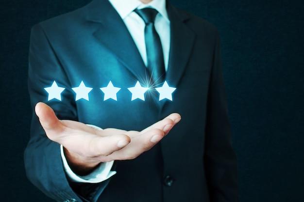 Uomo d'affari che tiene il concetto di cinque stelle