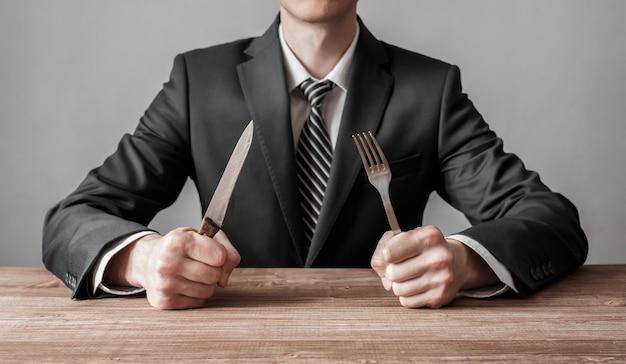 Uomo d'affari che tiene forchetta con coltello e pronto da mangiare