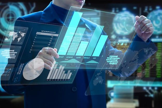 Uomo d'affari che tiene i touch screen di realtà aumentata del computer moderno virtuale futuristico che analizzano sulla gestione del rischio di investimento e sull'analisi di ritorno su investimento