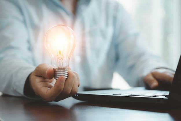 Uomo d'affari che tiene la lampadina incandescente e utilizza il computer portatile per inserire l'idea di strategia aziendale, idee di pensiero creativo e concetto di innovazione.