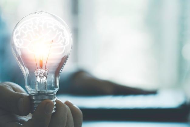 Uomo d'affari che tiene la lampadina incandescente con il cervello e utilizza il laptop del computer per inserire l'idea di strategia aziendale, idee di pensiero creativo e concetto di innovazione.