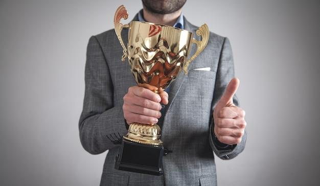Uomo d'affari che tiene trofeo d'oro