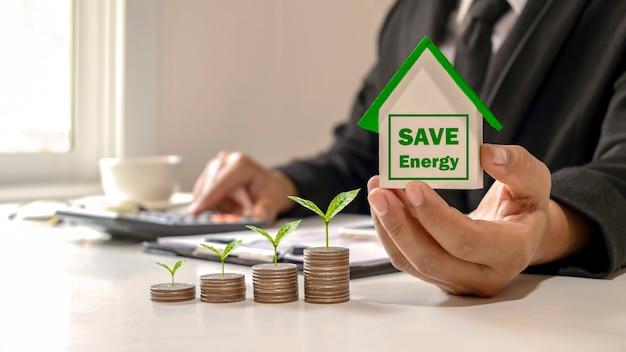Uomo d'affari che tiene un modello di serra per risparmiare energia e alberi che crescono su una pila di idee ipotecari
