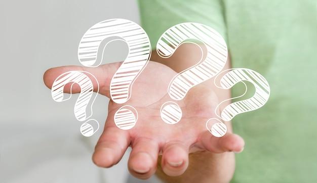 Uomo d'affari che tiene i punti interrogativi disegnati a mano in sua mano