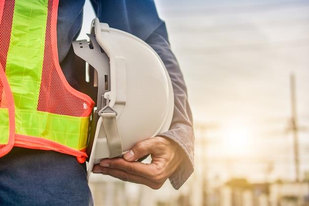 Uomo d'affari che tiene il fondo della costruzione della proprietà della costruzione del casco, concetto dell'ingegnere supervisor foreman