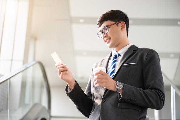 Uomo d'affari che tiene la tazza di caffè calda e che per mezzo del suo telefono