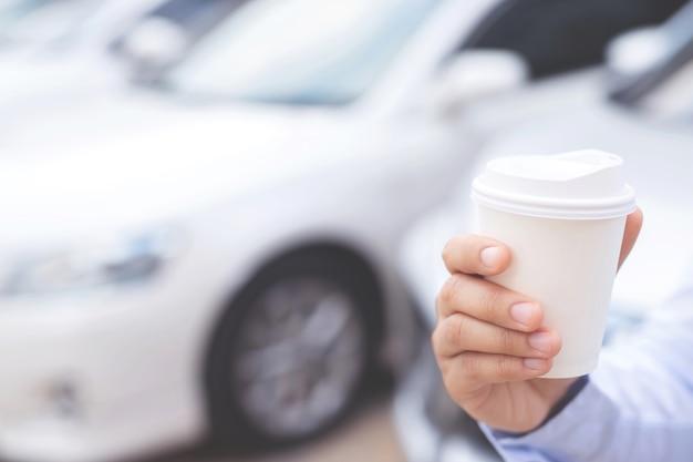 Un uomo d'affari con in mano una tazza di caffè caldo, ha bevuto il caffè prima di guidare.