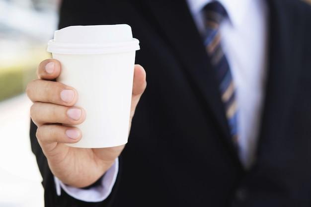 Un uomo d'affari che tiene una tazza di caffè calda, ha bevuto il caffè prima del lavoro la mattina