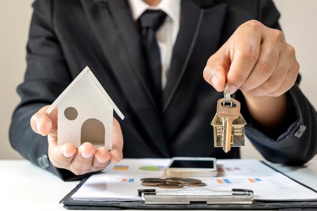 Uomo d'affari che tiene le chiavi di casa e la casa progetta il concetto finanziario mutuo e mutuo immobiliare