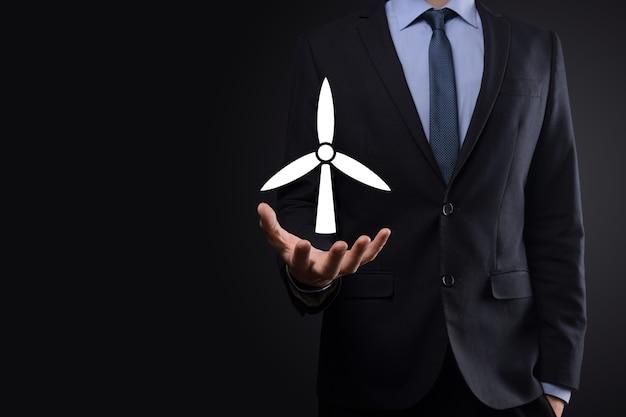 Uomo d'affari che tiene un'icona di un mulino a vento che produce energia ambientale. sfondo scuro