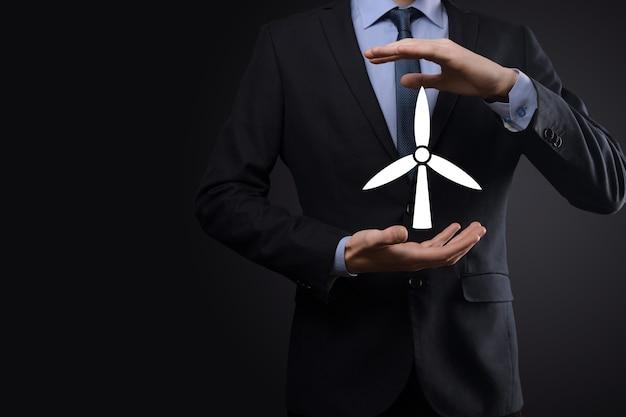 Uomo d'affari che tiene un'icona di un mulino a vento che produce energia ambientale. sfondo scuro.