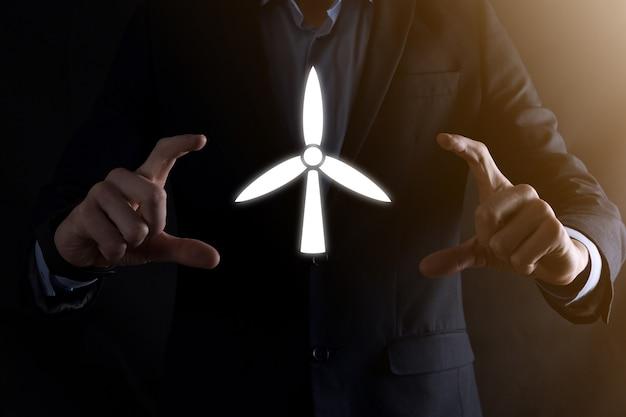 Uomo d'affari che tiene un'icona di un mulino a vento che produce energia ambientale.